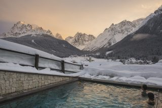 Berghotel Sexten WinterThe open swimmingpool and the Dolomites of Sesto at Berghotel in Sesto